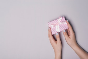 Elevated view of hand holding gift box against gray background