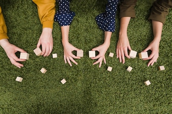 Elevated view of hand's holding blank wooden blocks over the green grass