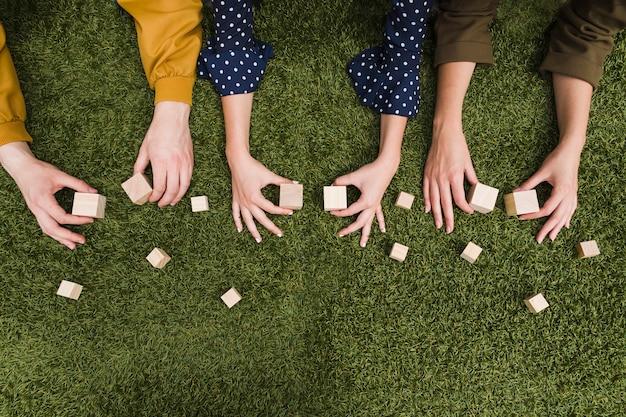 緑の草の上に手の空の木製ブロックを保持する上昇したビュー