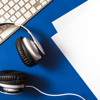 Elevated view of headphone; paper and keyboard on blue background
