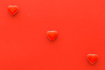 Elevated view of heart shape candies on red background