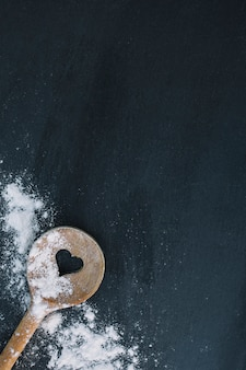 Elevated view of heart shape spoon and flour on black surface