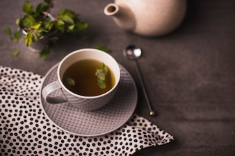 Elevated view of herbal tea and polka dotted textile on table