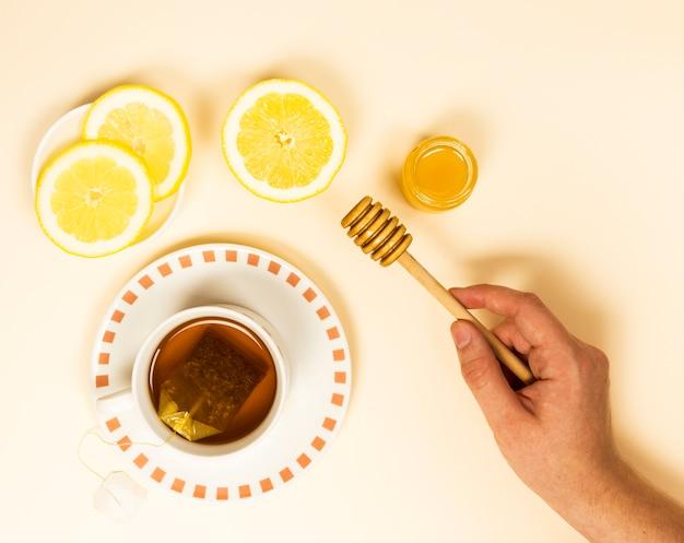 健康茶とレモンスライスに近い蜂蜜ディッパーを持っている人間の手の立面図