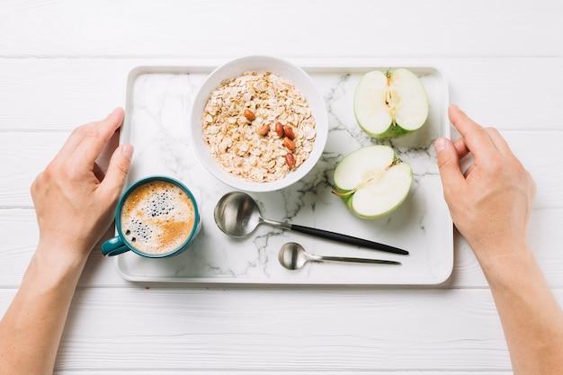 白い背景の上においしい食事のトレイを保持している人間の手の立面図