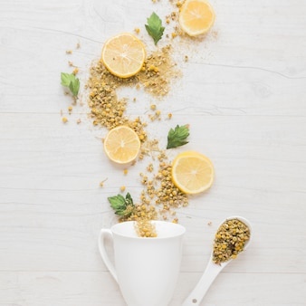 Elevated view of ingredients of lemon tea with ceramic cup and spoon