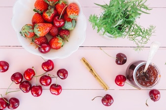 Elevated view of jam; cherries and rosemary near fresh strawberries in bowl