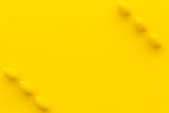 Elevated view of lemon candies on yellow backdrop