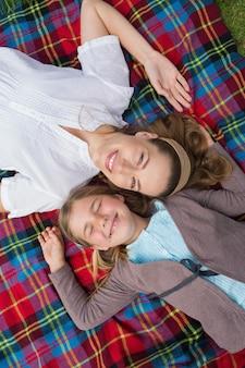 公園に横たわっている母と娘の高台