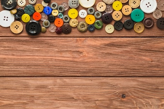 Elevated view of multi colored buttons on wooden background