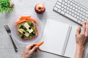 Elevated view of person's hand holding healthy food while working on keyboard