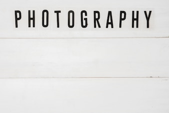 Elevated view of photography text over white wooden table