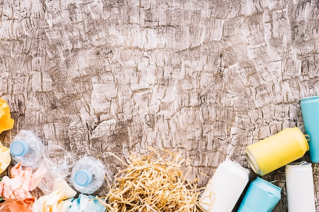 나무 표면에 플라스틱 병, 구겨진 된 종이 및 깡통의 높은보기