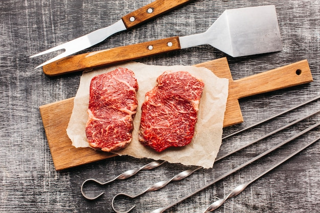 Повышенные вид сырой стейк и барбекю на деревянной текстурированной поверхности
