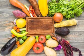 Elevated view of raw vegetables surrounding wooden chopping board