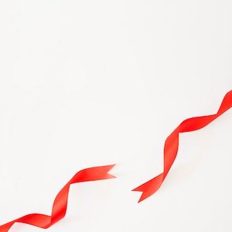 Elevated view of red satin ribbons on white backdrop