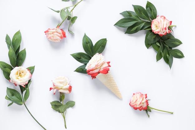 Повышенный вид розы в вафельном мороженое конус на белом фоне