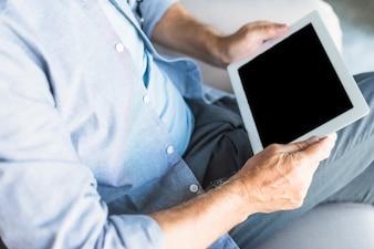 デジタルタブレットを持っている高齢者の高められたビュー
