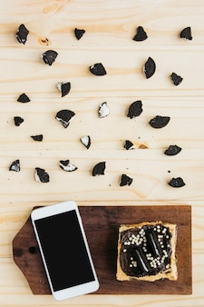 Elevated view of smartphone with pastry near pieces of cookies