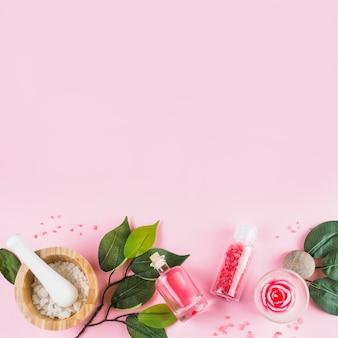 Повышенный вид спа-продукции и листьев на дне розовой поверхности