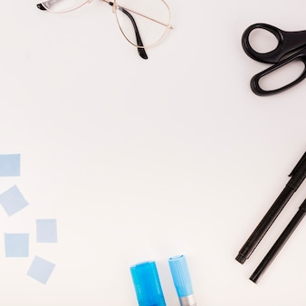 Elevated view of spectacles; pen; scissors and adhesive notes on white background