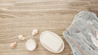 Elevated view of sponge; seashell; soap and moisturizing cream on wooden surface
