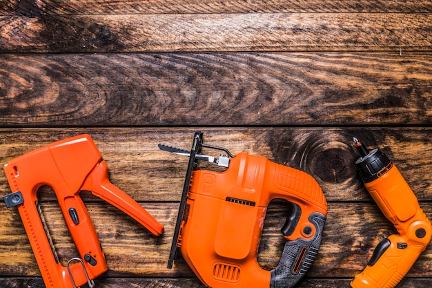 Повышенный вид штапельного пистолета, электрический лобзик и бурильщик на деревянном фоне