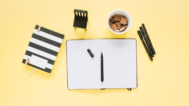Повышенный вид канцелярских товаров и стекла конфет на желтом фоне