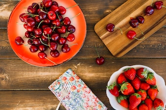 Elevated view of strawberries and cherries on wooden background