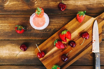 Elevated view of strawberries; cherries and knife on cutting board