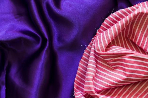 Повышенный вид ткани полос ткани и шелковистой фиолетовой ткани