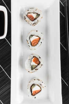 Elevated view of sushi arranged on white tray over the place mat