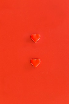 Elevated view of two heart shape candies on red background