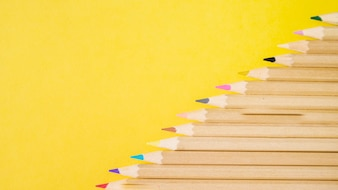Elevated view of various colorful pencils on yellow background