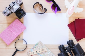 Elevated view of various traveling equipments and blank white paper on wooden backdrop