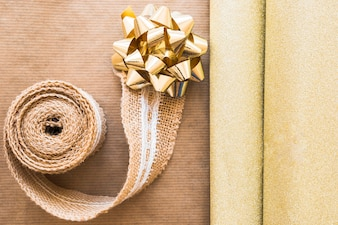Elevated view of weaving ribbon and golden bow with shiny gift paper