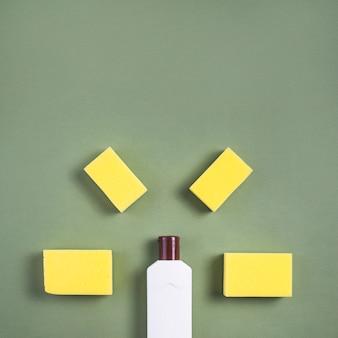 녹색 배경에 흰색 병 및 노란색 스폰지의 높은보기