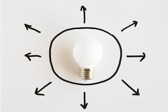 Elevated view of white light bulb surrounded with arrow symbols showing various directions