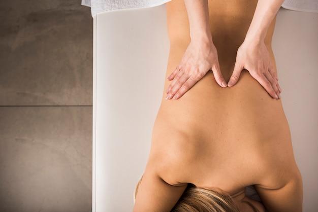 Повышенный вид женщины, получающей массаж спины от массажа в спа