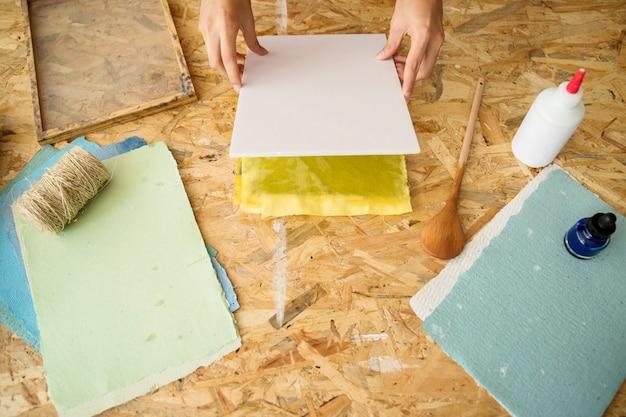 木製の机の上に紙パルプを覆う女性の手の上昇したビュー