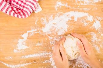 Повышенный взгляд на женскую руку, готовящее тесто