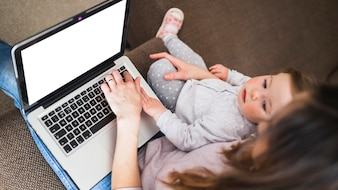 Elevated view of woman with her daughter using laptop with blank white screen