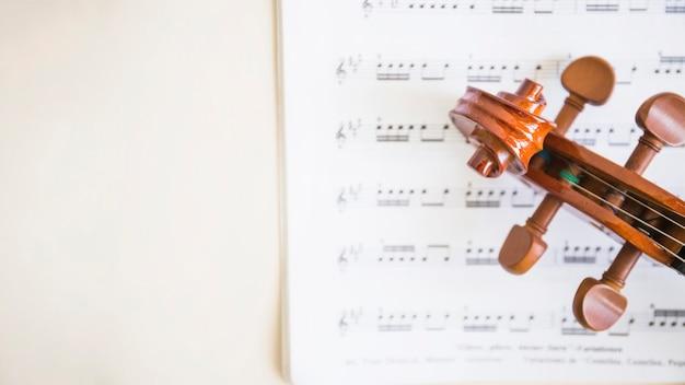 Повышенный вид деревянной свитки скрипки и струнных на музыкальных нотах