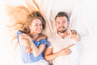 Elevated view of young couple lying on bed pointing finger upward