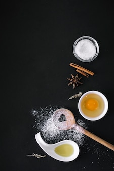 Elevated view of oil; egg; flour; sugar; grains; spices and heart shape wooden spoon on black surface
