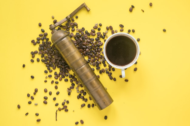 Elevated view of old coffee grinder and coffee beans with hot coffee on colored backdrop