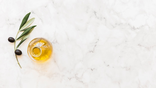 Elevated view of olive oil bottle with twig on marble background