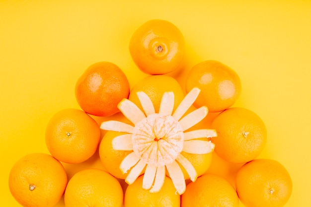 An elevated view of an orange fruits on yellow background