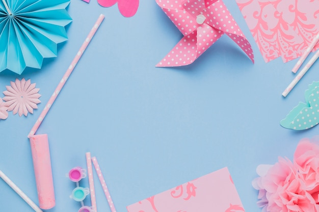 Elevated view of origami crafts art and straw on blue background
