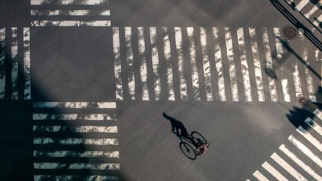 Повышенный вид на байкера на пешеходном переходе на перекрестке дорог японии. аэрофотоснимок езды на велосипеде по пешеходному переходу. центр азии. метрополитен токио